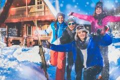 Les amis passent des vacances d'hiver au cottage de montagne Photo stock