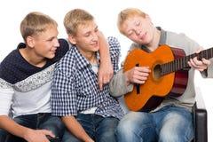 Les amis passent le temps libre jouant la guitare Image libre de droits