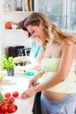 Les amis préparant la salade, une femme est enceinte Photo libre de droits