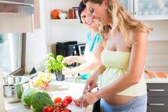 Les amis préparant la salade, une femme est enceinte Images libres de droits
