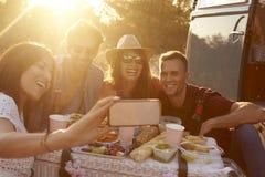 Les amis prenant le selfie au pique-nique près du camping-car, se ferment  Image libre de droits