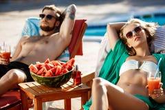 Les amis prenant un bain de soleil, cocktails potables, se trouvant sur des cabriolets s'approchent de la piscine Image stock