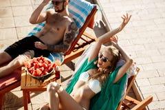 Les amis prenant un bain de soleil, sourire, se trouvant sur des cabriolets s'approchent de la piscine Photos stock