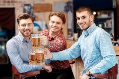 Les amis prennent une bière au bar Image libre de droits