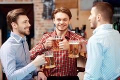 Les amis prennent une bière au bar Photo libre de droits