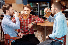 Les amis prennent une bière au bar Images libres de droits