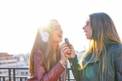 Les amis réunissent des firls chantant le karaoke à la terrasse de toit Image libre de droits
