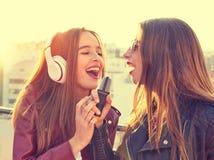Les amis réunissent des firls chantant le karaoke à la terrasse de toit Photos stock