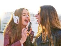 Les amis réunissent des firls chantant le karaoke à la terrasse de toit Photographie stock libre de droits