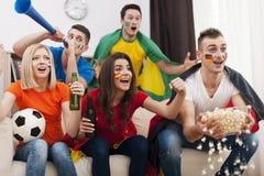 Les amis regardant la TV folâtre le jeu Images stock