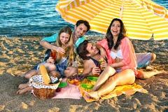 Les amis riants ont le pique-nique sur la plage Photos stock
