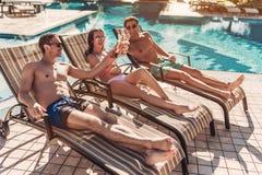 Les amis s'approchent de la piscine de swimmimg Photo stock