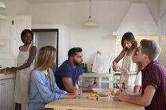 Les amis s'asseyant à la table, une prépare la nourriture, une verse le vin Photographie stock libre de droits