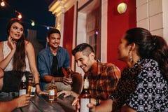 Les amis s'asseyant autour d'une table au dessus de toit font la fête Image stock