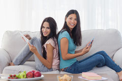 Les amis s'asseyant de nouveau au dos utilisant leurs comprimés souriant à sont venus Photo libre de droits
