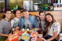 Les amis s'asseyant par la nourriture et la boisson ont servi sur la table dans le restaurant Images libres de droits