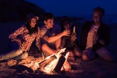 Les amis s'asseyant sur la plage font tinter des verres près du feu Images stock