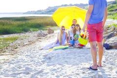 Les amis s'asseyant sur le sable à la plage à l'été pique-niquent Photos stock