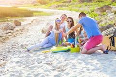 Les amis s'asseyant sur le sable à la plage à l'été pique-niquent Photo libre de droits