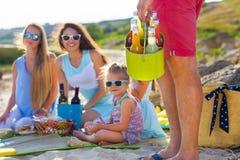 Les amis s'asseyant sur le sable à la plage à l'été pique-niquent O Image libre de droits