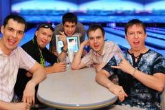 Les amis s'asseyent à la table et à la grimace dans le bowling Images libres de droits