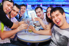 Les amis s'asseyent à la table et boivent de la bière dans le bowling Photo stock
