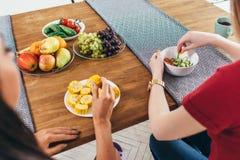 Les amis s'asseyent à la table, parlent et mangent des légumes à la main Photographie stock