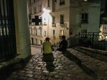 Les amis s'asseyent sur l'étape pavée en cailloutis par dessus d'un trottoir de Montmartre, Paris, France, une soirée d'été Photographie stock libre de droits