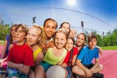 Les amis s'asseyent sur la cour de match de volley tenant la boule Photo stock