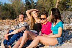 Les amis s'asseyent sur la plage dans le sable et rire Image stock
