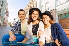 Les amis s'asseyent sur le banc tenant ensemble le comprimé Photo stock