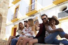 Les amis s'asseyent sur le mur lisant un guide et prenant des selfies Images libres de droits