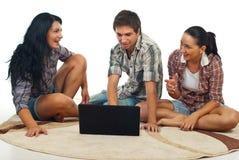Les amis s'asseyent sur le tapis avec l'ordinateur portatif Photo stock
