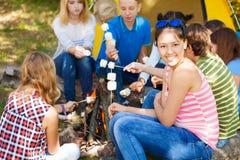 Les amis s'asseyent sur le terrain de camping avec des bâtons de smores Photos stock