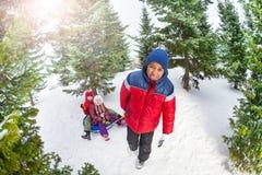 Les amis s'asseyent sur le tube et autre de neige les tirant Photographie stock libre de droits