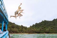 Les amis sautant à la mer du bateau, ayant l'amusement ensemble, échouent des vacances tropicales Photos stock