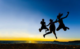 Les amis sautant à la silhouette de coucher du soleil Photo stock