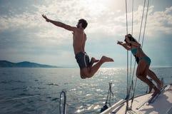 Les amis sautant dans l'eau d'un bateau à voile Photos stock
