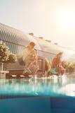 Les amis sautant dans la piscine Photos libres de droits