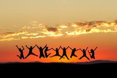 Les amis sautant en ciel de coucher du soleil Photos libres de droits