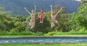Les amis sautant ensemble dans la piscine à la station de vacances 4k banque de vidéos