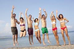 Les amis sautant sur la plage Photographie stock libre de droits