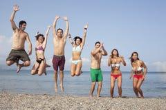 Les amis sautant sur la plage Photos libres de droits
