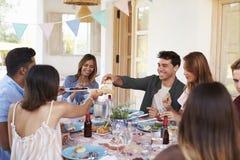 Les amis se servant à un dîner de patio, se ferment  Photos stock
