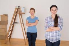 Les amis se tenant avec des bras ont croisé dans une nouvelle maison Photographie stock libre de droits