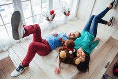 Les amis se trouvent à côté des têtes opposées sur le plancher en bois photographie stock libre de droits