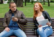 Les amis sont amusement pour observer quelque chose à un téléphone portable et comprimé Images libres de droits
