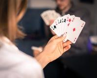 Les amis sont des cartes de jeu ensemble à la maison La femme tient les cartes dans des ses mains, homme à l'arrière-plan trouble photographie stock