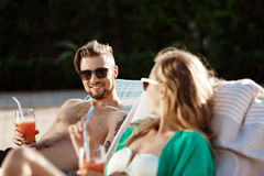Les amis souriant, cocktails potables, se trouvant sur des cabriolets s'approchent de la piscine Photo stock