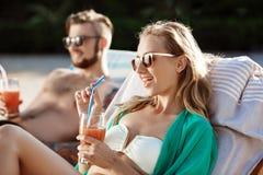 Les amis souriant, cocktails potables, se trouvant sur des cabriolets s'approchent de la piscine Image stock
